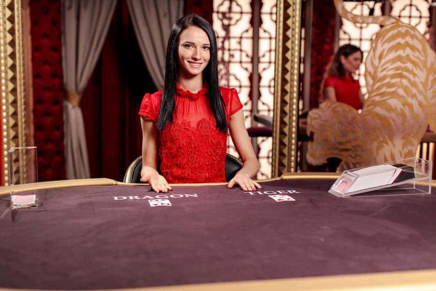 Live casino dealer in red dress pointing at cards