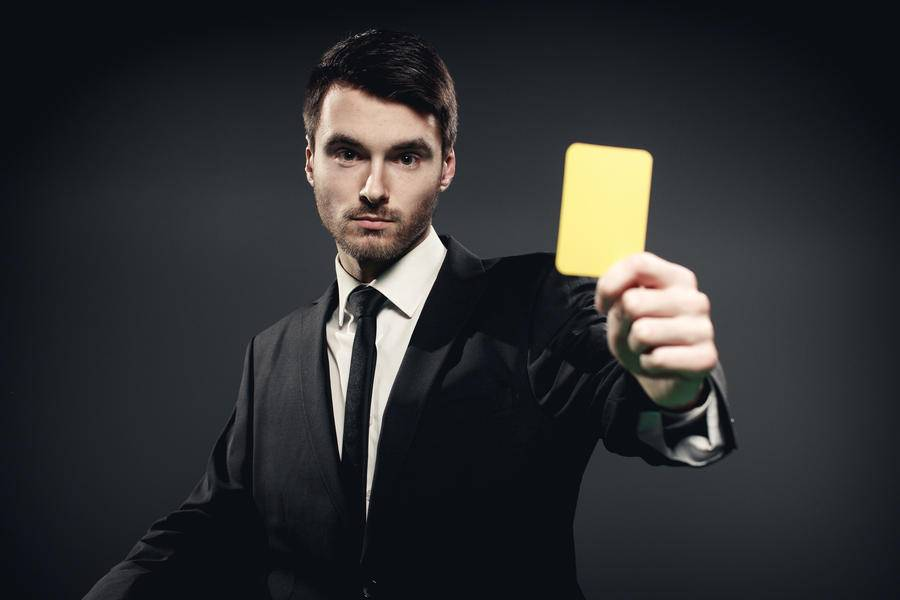 Suited man holding yellow card football